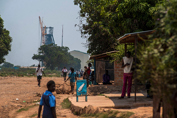 Schoolchildren walk along a dirt road near the shaft at the Mopani copper mine in Kitwe, Zambia. Photographer: Waldo Swiegers/Bloomberg via Getty Images