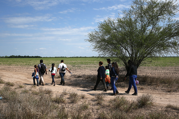 Central American immigrant families walk through the countryside after crossing from Mexico into the United States to seek asylum on April 14, 2016 in Roma, Texas. Photo by John Moore/Getty Images
