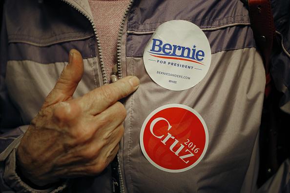 A person displays campaign stickers for Senator Ted Cruz, and Senator Bernie Sanders. Luke Sharrett/Bloomberg via Getty Images