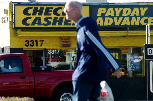 UNITED STATES - NOVEMBER 23: A pedestrian walks by a Payday Advance shop on El Cajon Blvd. in San Diego, California on Tuesday, November 23, 2004. Since emerging from rural Tennessee in 1993, payday lending has expanded beyond the fringes of the consumer finance industry. In 2003, the industry generated $6 billion in fee revenue from $40 billion in loans, according to Stephens Inc., a Little Rock, Arkansas-based investment bank. (Photo by Sandy Huffaker/Bloomberg via Getty Images)