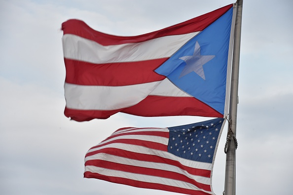The Puerto Rican and US flags are seen in the Old Town district in San Juan, Puerto Rico. PAUL J. RICHARDS/AFP/Getty Images