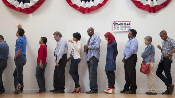 Voters waiting to vote in polling place. Photo credit: Getty