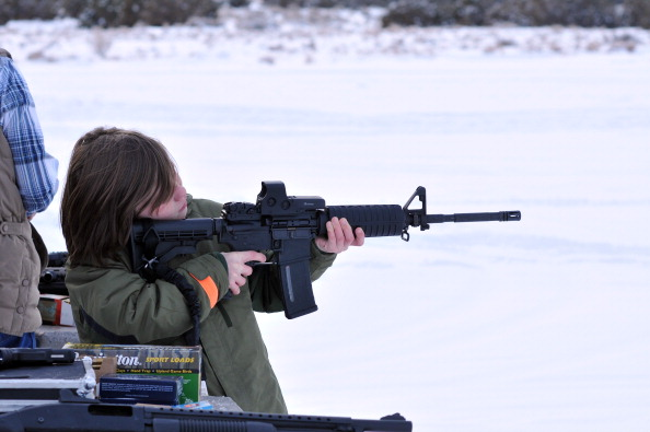 A young boy fires an AR-15 assault rifle at a shooting range.
