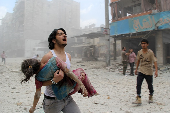 A man carries a young girl who was injured by government forces in Aleppo. BARAA AL-HALABI/AFP/Getty Images