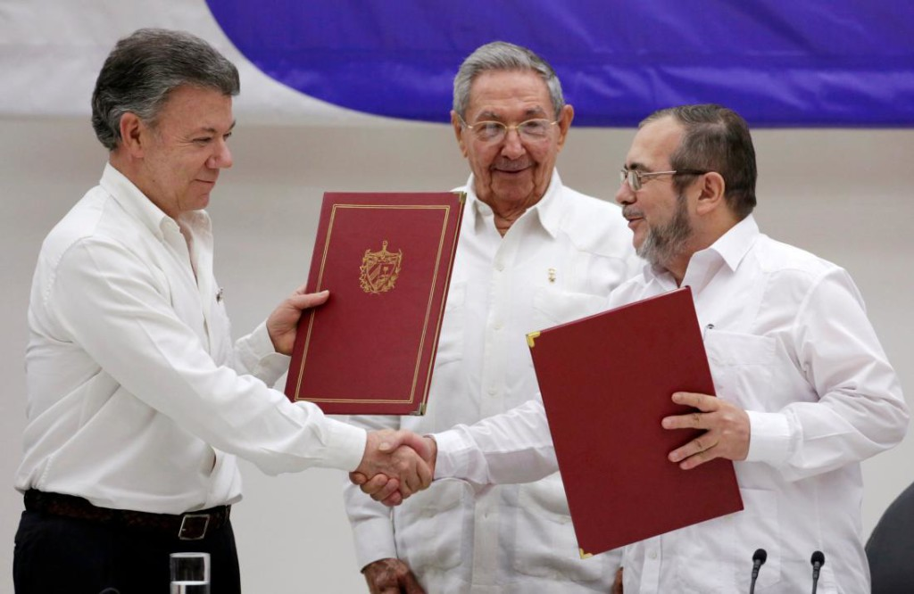 Colombia's President Juan Manuel Santos (L) and FARC rebel leader Rodrigo Londono, better known by his nom de guerre Timochenko, with Cuba's President Raul Castro (C), react after the signing of a historic ceasefire deal between the Colombian government and FARC rebels in Havana, Cuba, June 23, 2016. ADALBERTO ROQUE/AFP/Getty Images)