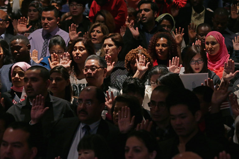 New Americans taking the Oath of Allegiance during a naturalization ceremony. Chip Somodevilla/Getty Images