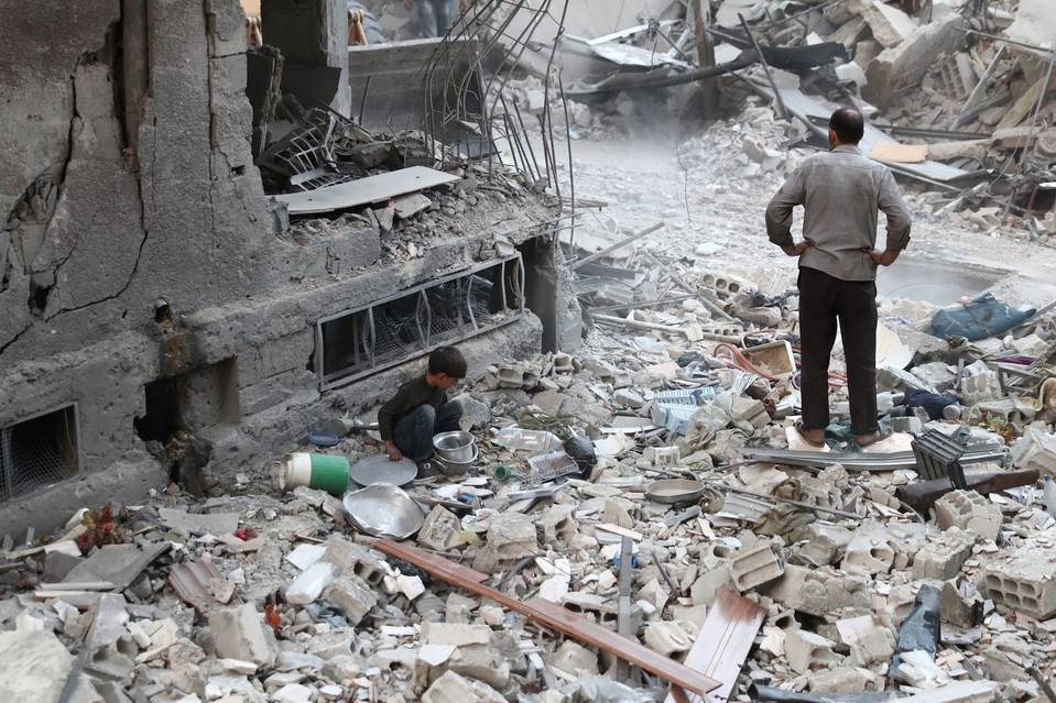 A Syrian boy collects items amidst the rubble of destroyed buildings. PHOTO: ABD DOUMANY/AGENCE FRANCE-PRESSE/GETTY IMAGES