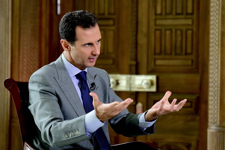 President Bashar Al-Assad talking to reporters in his office. Sanus