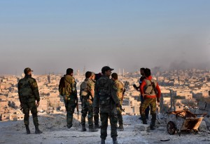Forces loyal to President Bashar al-Assad of Syria on top of a building overlooking Aleppo. They made large territorial gains Monday. Photo credit George Ourfalian/Agence France-Presse — Getty Images