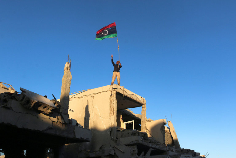 A Libyan fighter waved the country's flag from a house in Surt. Photo credit: Hani Amara/Reuters